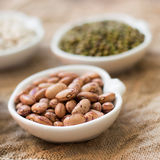 Assortment of legumes in bowls on wooden table Stock Photography