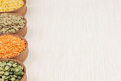 Assortment of lentils in a wooden bowls with copy space on white fabric background. Stock Photography