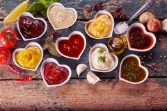 Assortment of marinades, sauces and dressings. In individual heart shaped bowls surrounded by scattered spices, herbs and condiments on rustic wood stock photography