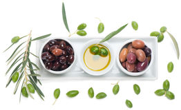 Assortment of marinated olives and olive oil  from above. Top view of marinated and fresh olives, olive oil in white bowls, on white Stock Image