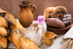 Assortment of milk bottles and bread loaves Stock Photo