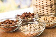 Assortment of mixed nuts and wicker basket on wood table background stock image