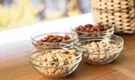 Assortment of mixed nuts and wicker basket on wood table background royalty free stock images