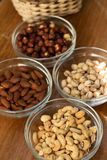 Assortment of mixed nuts and wicker basket on wood table background royalty free stock photos