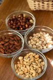 Assortment of mixed nuts and wicker basket on wood table background stock photography