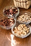 Assortment of mixed nuts and wicker basket on wood table background royalty free stock image