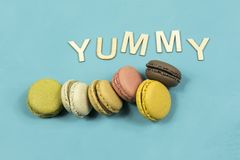 Assortment of multi-coloured macaroons on a blue background with the word yummy Royalty Free Stock Image