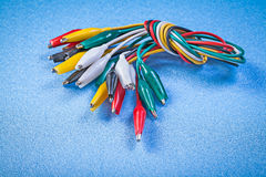Assortment of multicolored crocodile clip cables on blue backgro Royalty Free Stock Photo