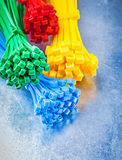 Assortment of multicolored plastic tying cables on scratched met Stock Photos