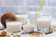 Assortment of non dairy vegan milk and ingredients. On white wooden background. Healthy drinks concept. Copy space Stock Photo