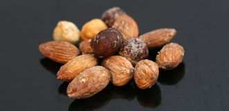 Assortment of nuts on black  background. Pic Assortment of nuts on bright background Royalty Free Stock Photos