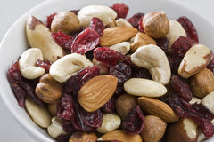 Assortment of nuts and dried cranberries. In white dishware Stock Photography
