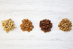 Assortment of nuts on white wooden background. Cashew, hazelnuts, walnuts, almonds. Top view stock photo