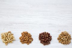 Assortment of nuts on white wooden background. Cashew, hazelnuts, walnuts, almonds. Top view. Copy space and text area stock photos