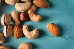 Assortment of nuts in wooden bowl on blue wooden table. Cashew, hazelnuts, almonds royalty free stock photos