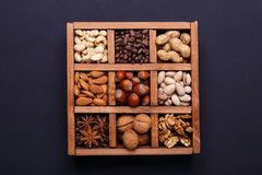 Assortment of nuts in a wooden box on a black background - healthy snack. stock image