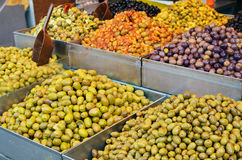 Assortment of olives, pickles and salads on market stand Stock Photo