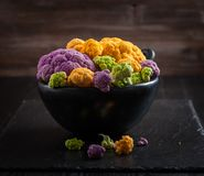 Assortment of organic cauliflower. From local market on wooden background Royalty Free Stock Photo