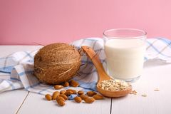 Assortment of organic vegan non dairy milk from nuts in glass on a wooden table on pink background. Coconut, almond nuts, spoon of. Oat flakes. Food and drink royalty free stock photography