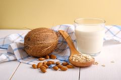 Assortment of organic vegan non dairy milk from nuts in glass on a wooden table on yellow background. Coconut, almond nuts, spoon. Of oat flakes. Food and drink stock image