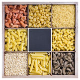 Assortment of pasta in a wooden box and a blackboard Royalty Free Stock Photography