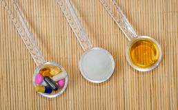 Assortment of pharmaceutical preparations on spoons, tablets, capsules, syrup and powder. On the bamboo mat. royalty free stock photo