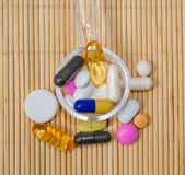 Assortment of pharmaceutical preparations, tablets and capsules on a spoon, on a bamboo mat royalty free stock photography