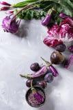 Assortment of purple vegetables. Assortment raw organic of purple vegetables mini eggplants, spring onion, beetroot, radicchio salad, plums, kohlrabi, flower Royalty Free Stock Photo