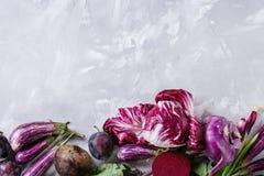Assortment of purple vegetables. Assortment raw organic of purple vegetables mini eggplants, spring onion, beetroot, radicchio salad, plums, kohlrabi, flower Stock Photo