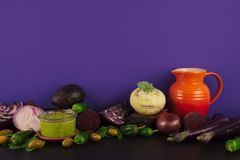 Assortment of raw organic purple and green vegetables. Assortment of raw organic purple and green vegetables on violet background Stock Photography