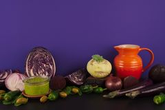Assortment of raw organic purple and green vegetables. Assortment of raw organic purple and green vegetables on violet background Royalty Free Stock Photo