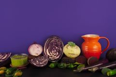 Assortment of raw organic purple and green vegetables. Assortment of raw organic purple and green vegetables on violet background Stock Photos