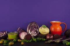 Assortment of raw organic purple and green vegetables. Assortment of raw organic purple and green vegetables on violet background Royalty Free Stock Images