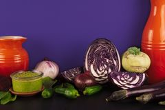 Assortment of raw organic purple and green vegetables. Assortment of raw organic purple and green vegetables on violet background Royalty Free Stock Photos