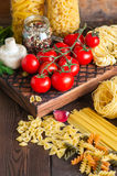 Assortment of raw types and shapes of italian pasta and wooden b stock photos