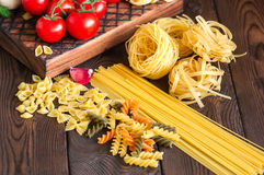 Assortment of raw types and shapes of italian pasta and wooden b stock photo