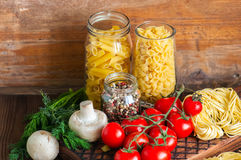 Assortment of raw types and shapes of italian pasta and wooden b stock image