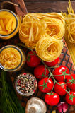 Assortment of raw types and shapes of italian pasta and wooden b royalty free stock images