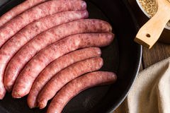 Assortment of raw uncooked sausages traditional Spanish type in iron cast pan, kitchenware Stock Photo