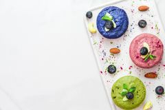 Assortment of raw vegan cheesecakes with matcha, acai, butterfly pea tea, berries, mint and nuts. healthy vegan food stock image