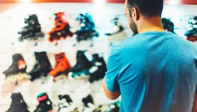 Assortment roller skates isolated in store shop, person choosing and buy color roller-skates on backgraund sun flare, healthy stock image