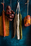 Assortment of sausages, Spanish charcuterie, wood cutting board, string with dry peppers Stock Photo