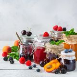 Assortment of seasonal berries and fruits jams in jars royalty free stock photo