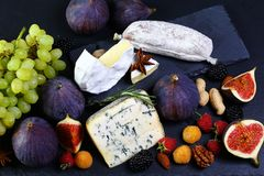 Assortment set snacks for wine on a shale board: cheese camembert or brie cheese, cheese Dor blue with figs, berries, nuts, baguet. Te and honey on the old table royalty free stock photography