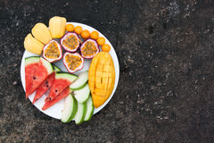 Assortment of sliced tropical fruits on plate. Background of dark stone. stock images