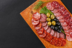 Assortment smoked sausage slices on cutting board Royalty Free Stock Images