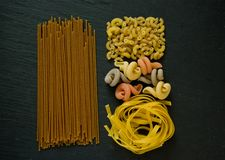Assortment of spaghetti pasta flat lay on a black stone backgrou royalty free stock images