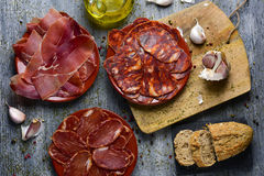 Assortment of spanish cold meats. High-angle shot of some plates with an assortment of different spanish cold meats as chorizo, cured pork tenderloin and serrano Royalty Free Stock Photos