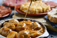 Assortment of spanish cold meats and tapas. Closeup of a plate with meatballs with cuttlefish and some plates with an assortment of different spanish cold meats Stock Photos