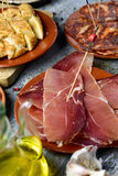 Assortment of spanish cold meats and tapas. Closeup of some plates with an assortment of different spanish cold meats, such as serrano ham and chorizo, a diced Royalty Free Stock Photography